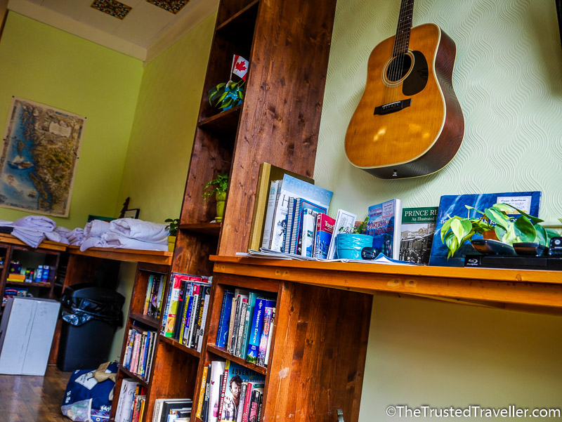 Books, a guitar and games in the living room - Hostel Review: HI Prince Rupert Pioneer Guesthouse - The Trusted Traveller
